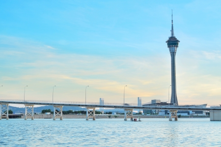 macau: Urban landscape of Macau with famous traveling tower under blue sky near river in Macao, Asia.