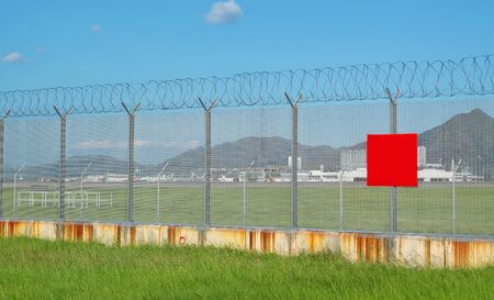 enclosures: metal fence in the nature and red board for text Stock Photo
