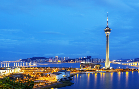macao: Urban landscape of Macau with famous traveling tower under blue sky near river in Macao, Asia.