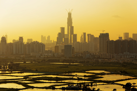 Air pollution scenic in countryside with building, rice field and yellow smoke in hong kong city at sunset photo