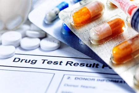 test: Syringe with glass vials and medications pills drug test report Stock Photo