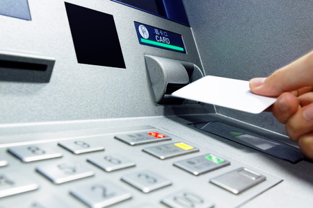 inserts: male hand businessman inserts credit card into the ATM and withdraws money
