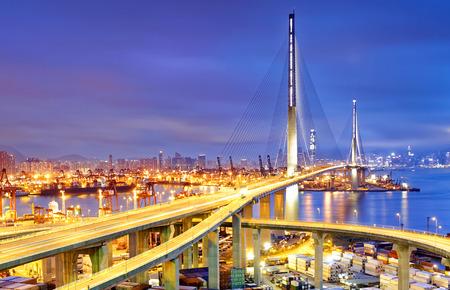 물류 수입 수출, 홍콩에 대한 일몰 스톤 커터 고속도로 다리 아래 조선소에서 크레인 다리 작업과 컨테이너화물 운송 선박