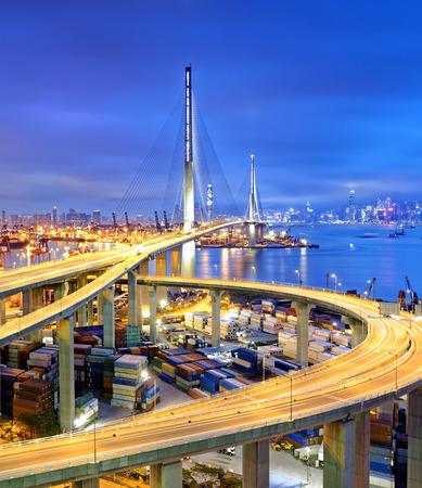 cielo y mar: Buque de carga de contenedores de carga con los que trabaja el puente grúa en el astillero bajo Canteros puente de la carretera al atardecer para Logística Import Export, Hong kong Foto de archivo