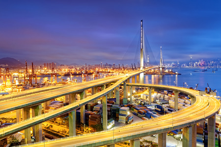 Container Cargo freight ship with working crane bridge in shipyard under Stonecutters highway bridge at sunset for Logistic Import Export, Hong kong Archivio Fotografico