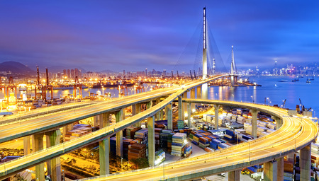 water transportation: Container Cargo freight ship with working crane bridge in shipyard under Stonecutters highway bridge at sunset for Logistic Import Export, Hong kong Stock Photo