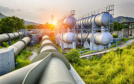 Glow luz del tanque de agua de la industria petroquímica en la puesta del sol. Foto de archivo