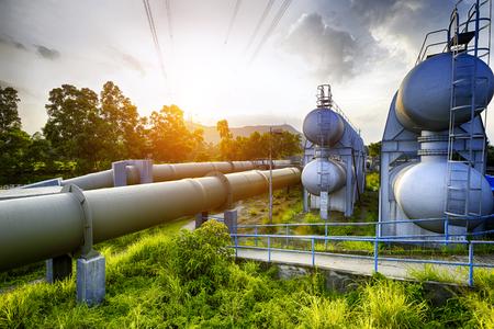 석양에 석유 화학 산업 물 탱크의 발광 빛