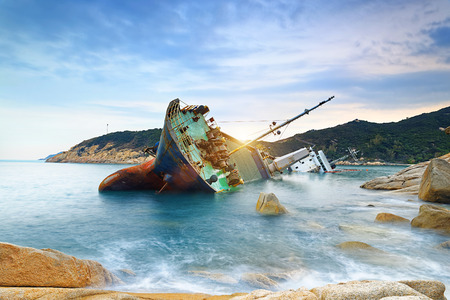 wrecked: shipwreck or wrecked cargo ship abandoned on sea bay Stock Photo