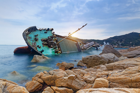 shipwreck or wrecked cargo ship abandoned on sea bay Stok Fotoğraf