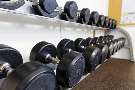 sports club: Sports dumbbells in modern sports club. Weight Training Equipment Stock Photo