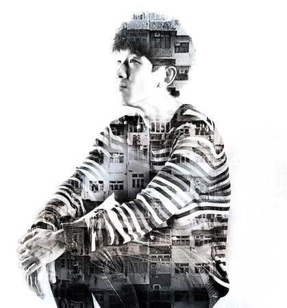 digital composite: double exposure asian sad man and city buildings Stock Photo