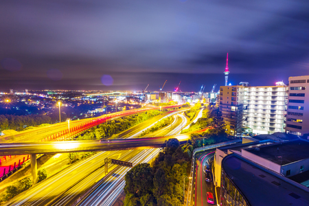 Long exposure shot of Auckland New Zealand transport at night with sky tower
