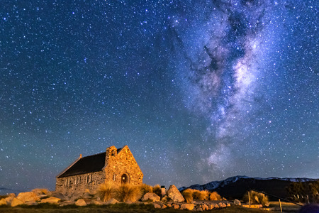 Via Lattea che sorge sopra la Chiesa del Buon Pastore, Tekapo NZ con Aurora Australis o la luce del sud che illumina il cielo. Rumore dovuto a ISO elevati; messa a fuoco morbida / DOF ridotto grazie all'ampia apertura utilizzata. Archivio Fotografico