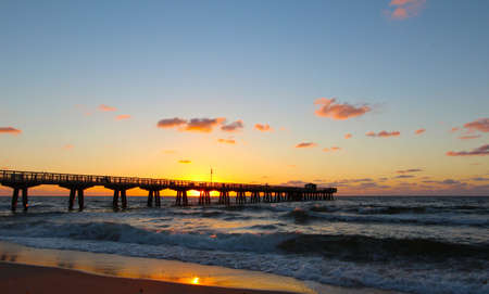 Fishing Pier backlit vy the rising sun Stock Photo