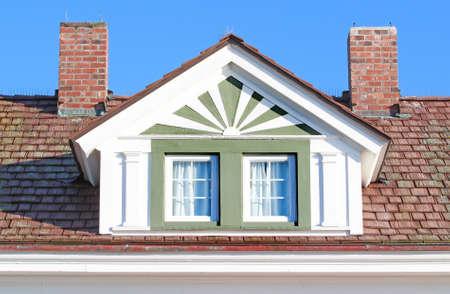 Roofline showing loft window and twin chimneys
