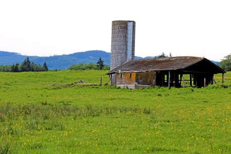 Old abandoned barn with grain silo photo