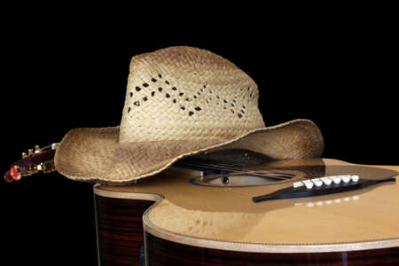 country music: acoustic guitar with hat isolated on black Stock Photo