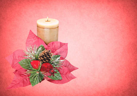 decorative red ponsettia with candle pine cone pomegranate and snow photo