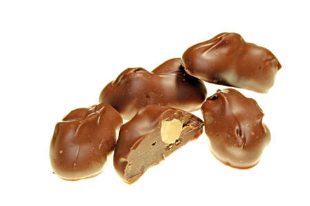 Chocolate covered macadamia nuts isolated on white