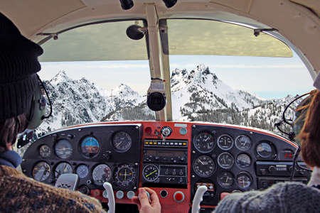view from over snow covered peaks while flying in small plane