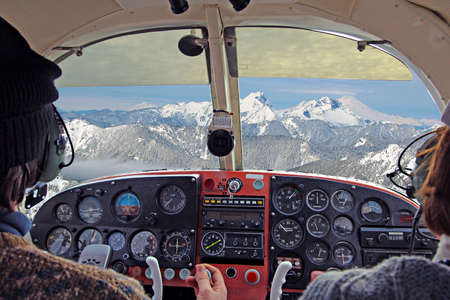 view from over snow covered peaks while flying in small plane photo