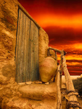 Dramatic scene of old clay wine pot, door and stairs photo