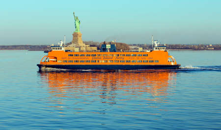 NEW YORK, USA, APRIL 19, 2015: Early morning sunlight reflecting off the Staten Island Ferry, a free ferry service between St. George on Staten Island and Whitehall Street in lower Manhattan