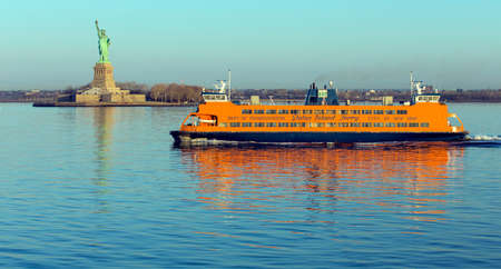 staten: NEW YORK, USA, APRIL 19, 2015: Early morning sunlight reflecting off the Staten Island Ferry, a free ferry service between St. George on Staten Island and Whitehall Street in lower Manhattan