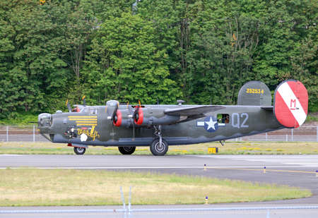 maching: SEATTLE - JULY 03, 2016: A vintage WWII B-24J Liberator bomber was seen flying over Seattle Editorial