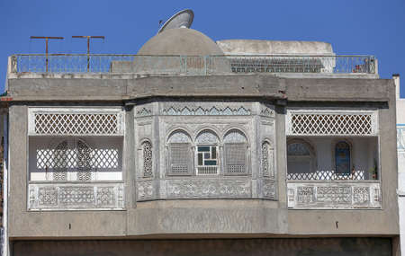 Mashrabiya or Shanashee is designed for women to look out upon men in the street but men cannot look upon the women. Found in residential houses, urban areas, street facing side of the house. Traditional Arab architecture. Stock Photo