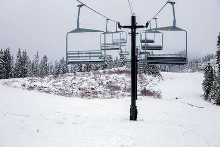 Ski lift with chairs on snowy slope