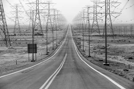 Stright weg geflankeerd aan beide zijden met hoogspanningsleidingen in zwart en wit Stockfoto