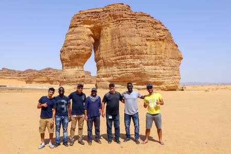 Madain Saleh, Al Ula, KSA - 2 Sep 2017: A group of tourists pose in front of the famous Elephant Rock near Al Ula in Saudi Arabia. Editorial