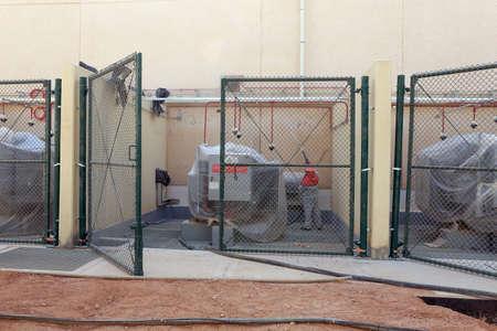 Sandblasting a wall inside an electical transformer bay Stock Photo