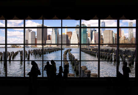 Manhattan from Brooklyn Bridge Park viewed through a window with people silhouetted in the fireground 写真素材 - 129412434