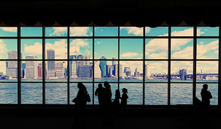 Manhattan and the East River with Effect viewed through a window with people silhouetted in the foreground 写真素材 - 129412113