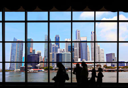 View of Singapore Skyline through a wndow with people silhouetted in the foreground 写真素材