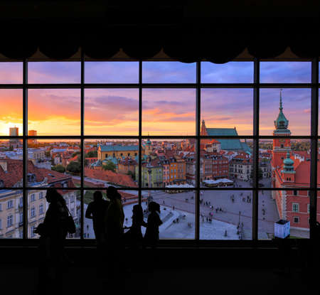 View of Warsaw old town and King Sigismunds Column viewed through a window with people silhouetted in the fireground Stock fotó