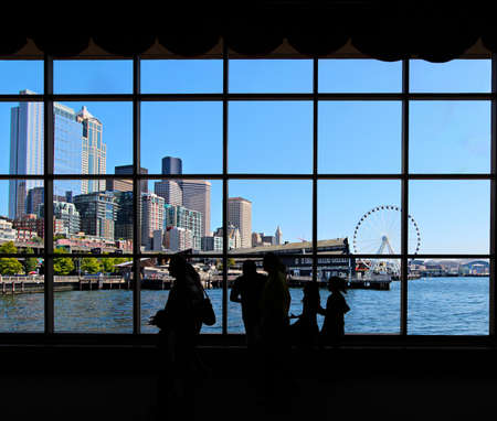 Seattle skyline, waterfront and great wheel through a window with people silhouetted in the foreground 스톡 콘텐츠