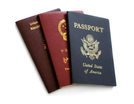 French, Chinese and US passports isolated on white background. Stock Photo