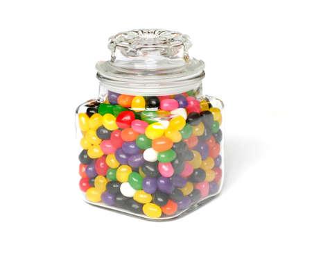 jarra: Caramelos de colores en un tarro de vidrio aislado en fondo blanco.