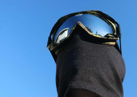 Masked Snowboarder on Blue sky background photo