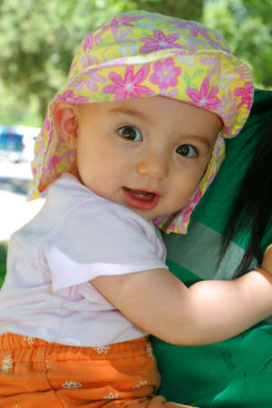 Baby girl smiling and holding mom Stock Photo