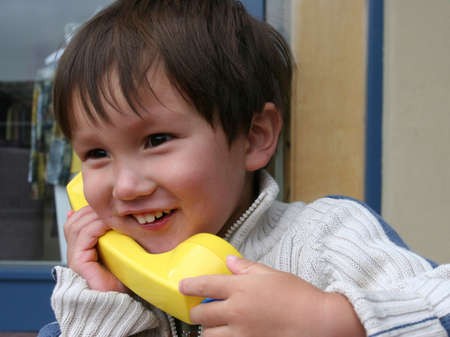 Smiling mixed Asian Caucasian 2 years old toddler calling home Stock Photo