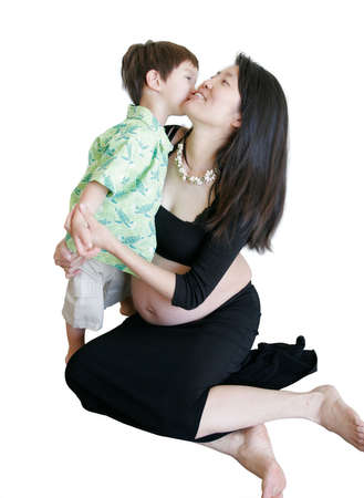 Mixed asian-caucasian 3 years old kissing pregnant mom isolated on white background