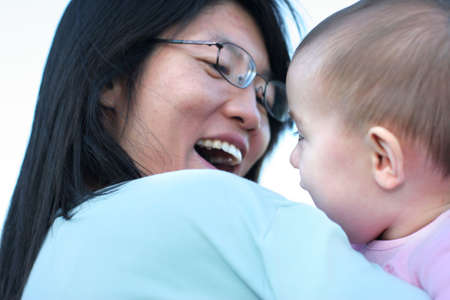 Ten months old baby smiling in mom's hand Stok Fotoğraf