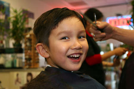 Three and half years old boy having a haircut photo