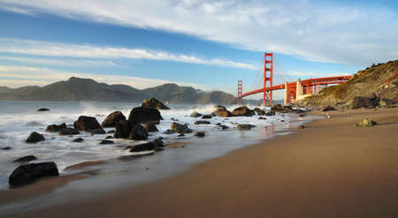Panoramic view of Golden Gate Bridge at sunset from a beach