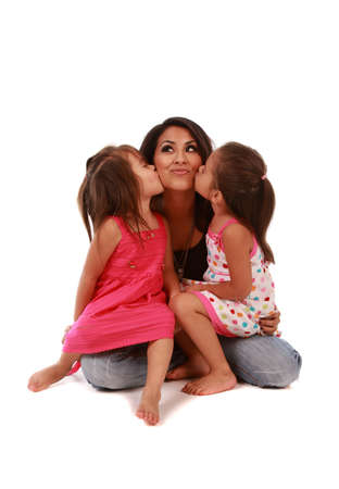 Two cute daughters kissing their mom on pure white background  Stok Fotoğraf